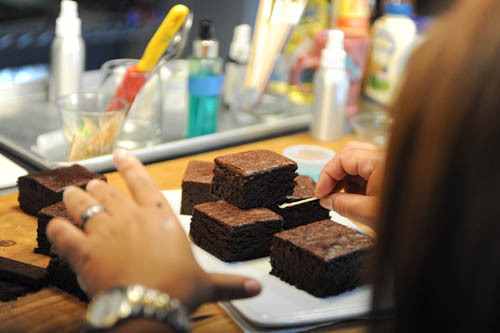 Here's a shot of Food stylist Ana Kelly working on the hero brownies in the kitchen, before bringing the plate over to the set.  Notice all the crap she needs to make me look like I know what I'm doing... :o)
